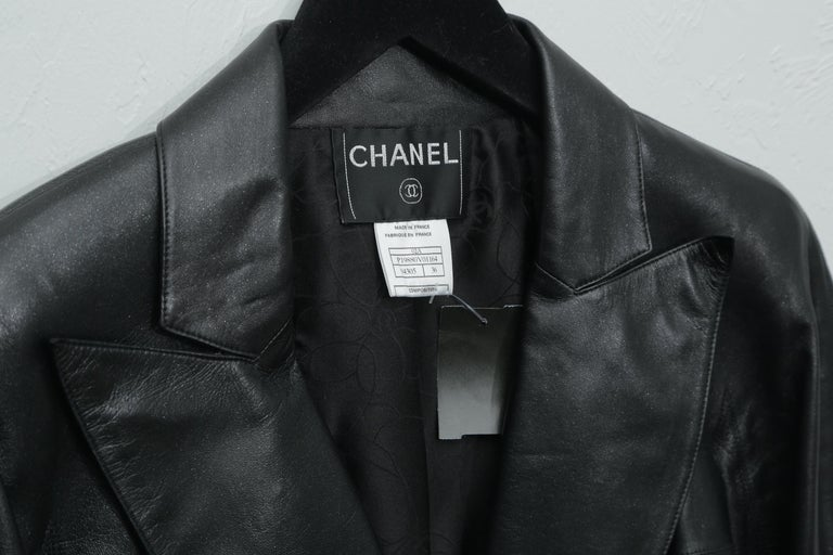 Chanel black metallic leather fitted jacket with three silver logo buttons and vertical pockets.  This is a truly stunning jacket in pristine condition. 4 small