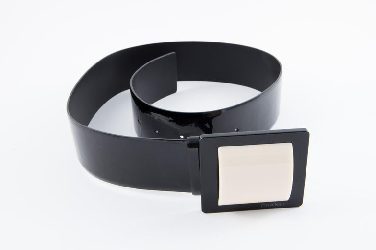 Gorgeous black patent lamb leather Chanel belt featuring an ivory and black large buckle, pitted Chanel on front buckle, and an adjustable buckle.  Width: 1.9in. (5cm) Length: 35,4in. (90cm) In excellent vintage condition. Made in France. We