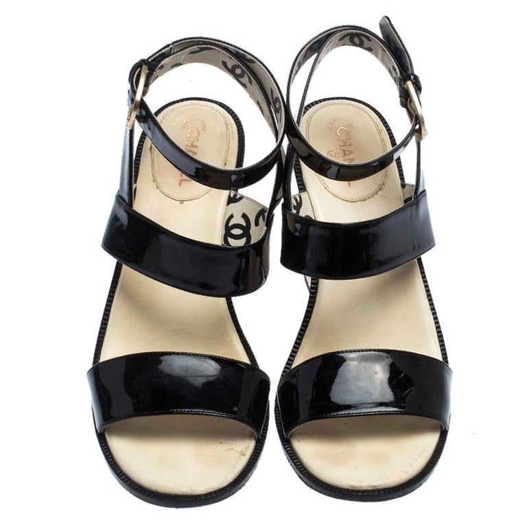 These fashionable sandals by Chanel are a 'closet delight' for any woman. These sandals are crafted from patent leather into a minimal design. They bring open toes, ankle strap buckle fastening and quilted block heels.  Includes: The Luxury Closet