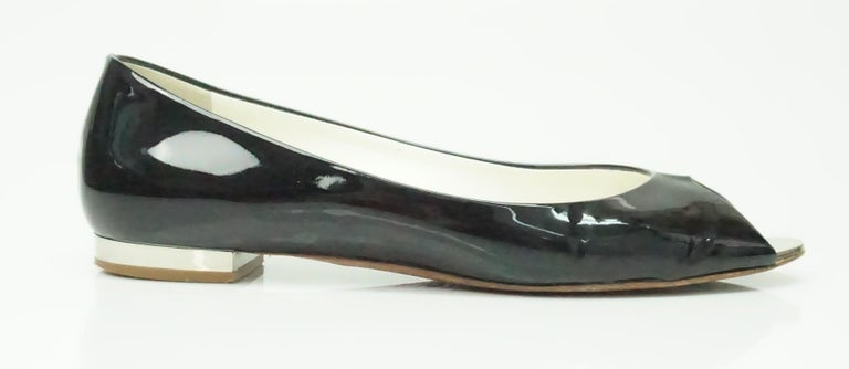 These adorable Chanel peep toe flats are patent leather with a short silver heel. They are in excellent condition and are a comfortable fit. They seem to only have been worn a few times.