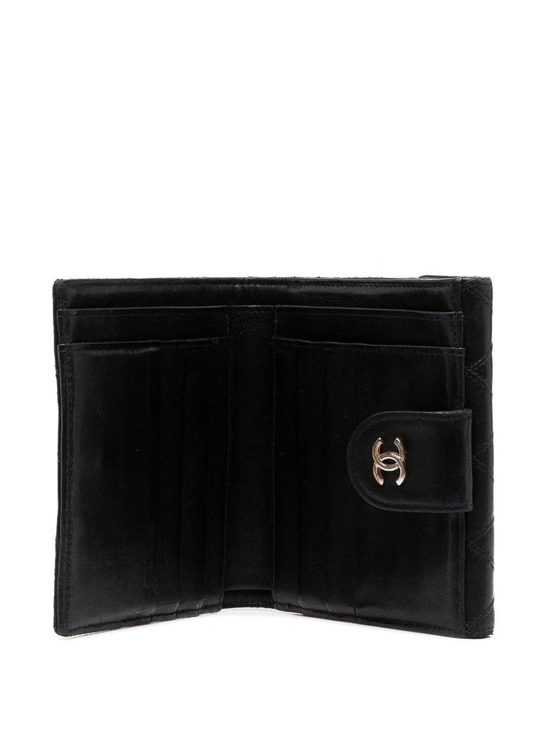 Chanel black quilted lamb wallet featuring signature interlocking CC logo,  multiple internal slip pockets, internal card slots, front flap pocket, leather lining. Length 3.9in (10cm) Width 4.3in. (11cm) Depth 0.8in. (2cm)  In good vintage