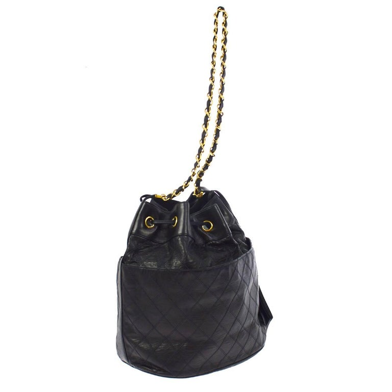 "- Vintage 80s Chanel black quilted lambskin bucket shoulder bag.   - Featuring gold-toned ""CC"" logo in front.   - Drawstring fastening.   - Gold-toned chain and black leather strap.   - Attached to a black lambskin leather pouch.   - Two exterior"