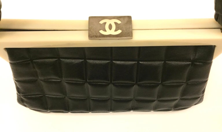 - Chanel black quilted leather chocolate bar handle bag from year 2002 to 2003 collection.   - Silver- tone hardware, single flat top handle, single pocket at interior and push-lock closure at top.  - Measurements: 23cm x 13cm x 10cm. Drop: 16cm.