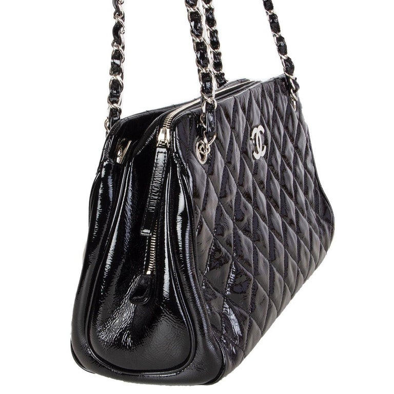 Chanel shoulder bag in black quilted patent leather with silver-tone CC and chain. Open pocket on the outside back. Two open pocket on each side with a zipper pocket in the middle. Lined in black leather with two open pockets against the front and a