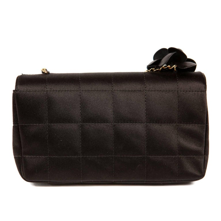 Chanel Black Satin Camellia Crossbody Bag- Pristine Condition  Elegant and timeless, this chic evening bag is smart addition to any collection.  Small black satin flap bag is quilted in square pattern.  Black fabric camellia flower sits atop the