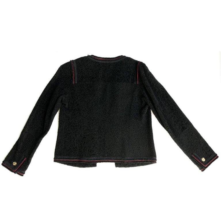 Black shearling two-pocket collarless jacket with red trim & ornate gold button accents. Made in France.  Size  42 French sizing  Condition  Excellent: worn once