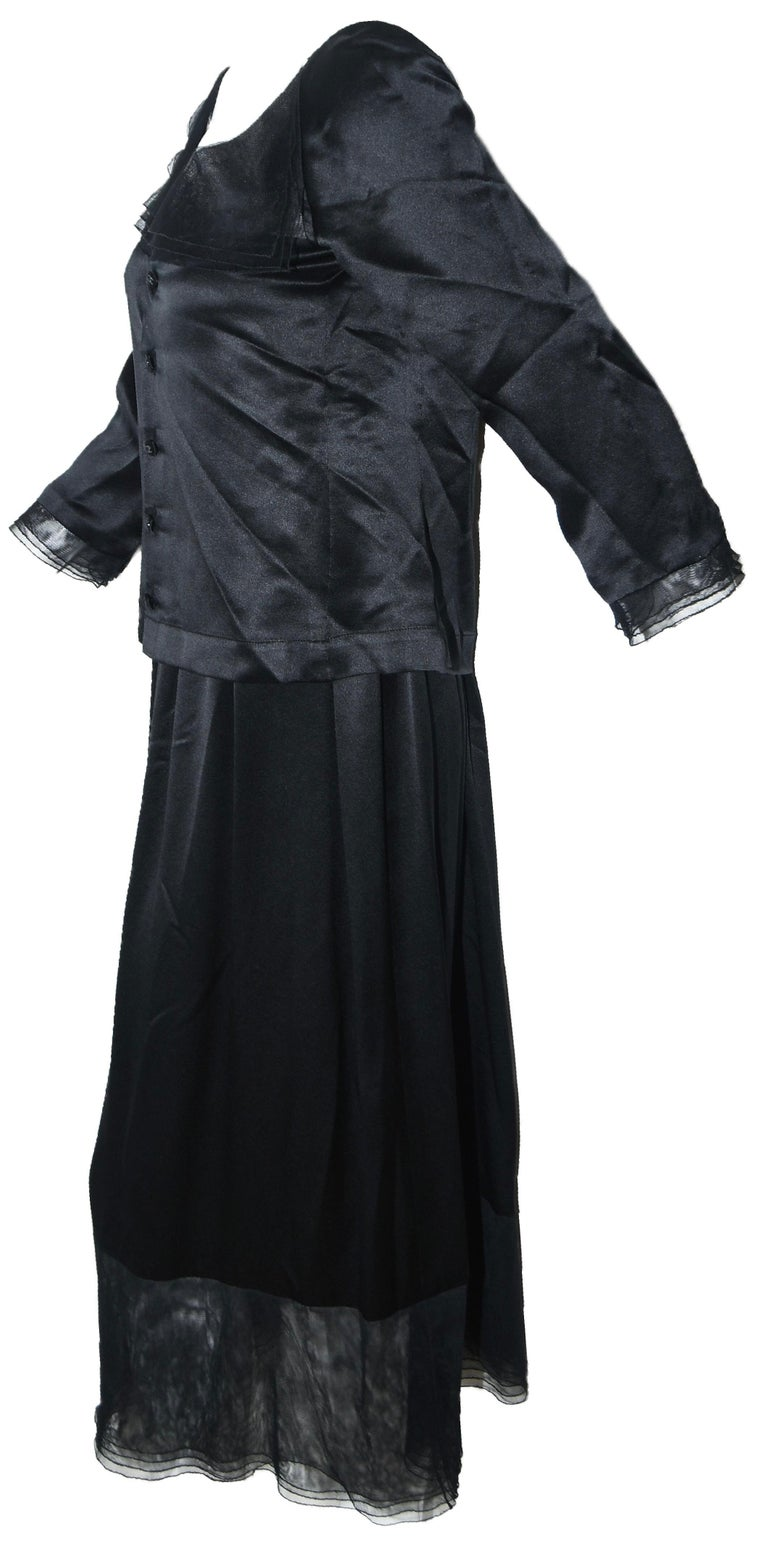 Chanel black silk two piece dress is composed of a 3/4 sleeve blouse contains 5 Chanel CC buttons at back for closure with mesh band across collar bone and sleeves finishing with lace ruffle.  The long skirt is gathered at waist and includes 4 black
