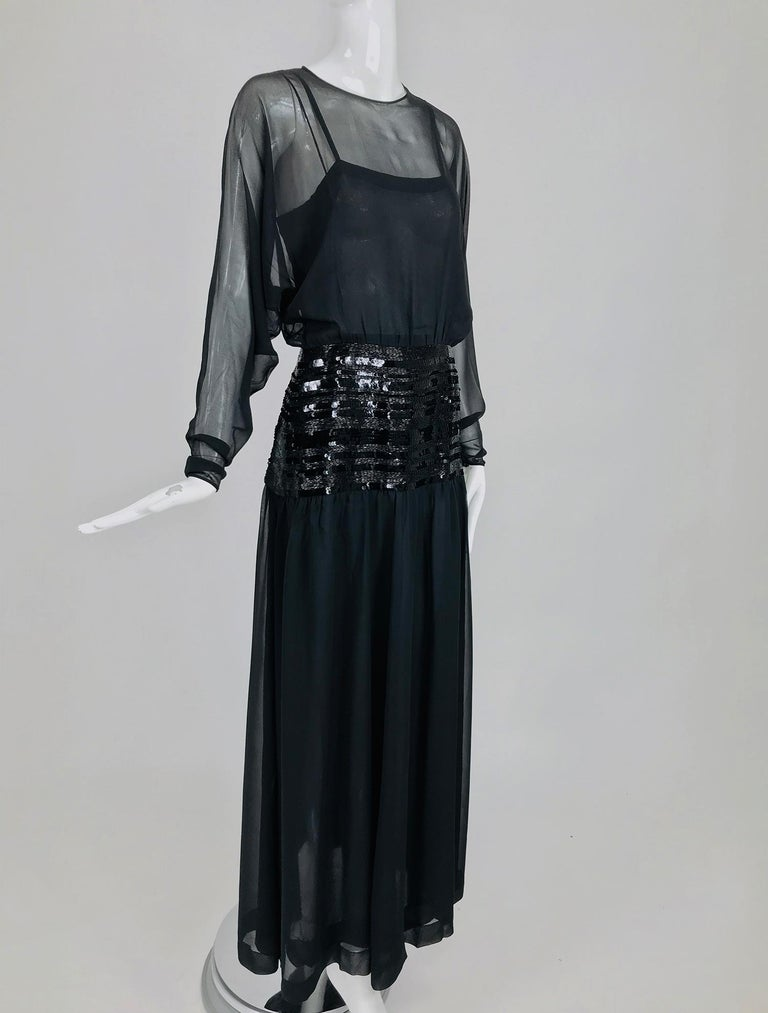 Chanel sheer black silk chiffon beaded hip, dolman sleeve evening gown from the 1980s. Gorgeous gown for any major event, this dress is truly spectacular.  Sheer black silk chiffon dress has a jewel neckline with long bat wing sleeves that taper to