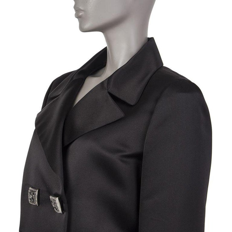 Chanel double-breasted satin blazer in black silk (100%). With notch collar, two pockets on the front sides, two-button cuffs, and signature chain around the inside of the hemline. Closes with embellished square buttons in silver metal with red and