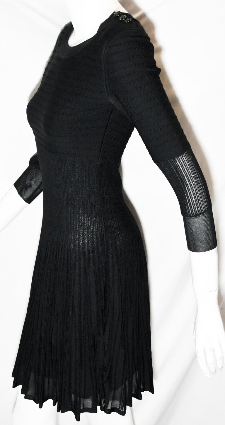 Chanel black knit silk blend dress from the 2009 cruise collection is a runway statement!  Composed with stretch silk and viscose on the upper torso then transitioning to silk ribbed pleats and flaring to a full skirt. The sleeves have the same