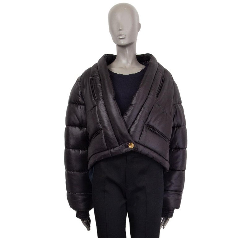 Chanel 'Paris-Moscow' double-breasted puffer jacket in black silk (100%). With v-neck, ribbed cuffs, CC crest patch on one arm, and four zipper pockets on the front. Closes with one black and golden CC crest button and one concealed butoon on the