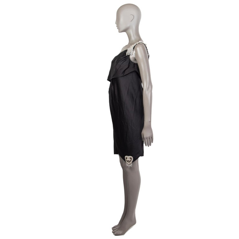 Chanel embellished one-shoulder mini dress in black silk (100%) with a chanel 2008 beaded application detail on the right bottom corner. Closes on the side with a concealed zipper along with six cc engraved clear diamond shaped beads. Unlined. Has