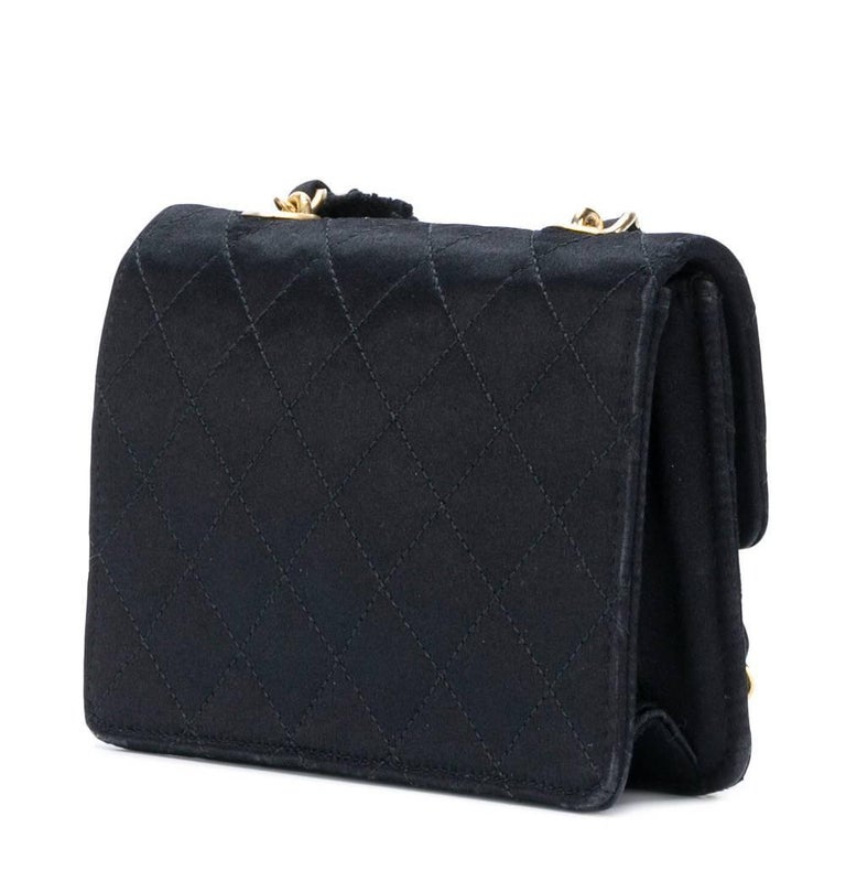 Elegant Chanel matelassé flap bag in black silk. It features features a gold-tone chain, elongated to be comfortably worn hanging from the shoulder or wrapped around the hand, a foldover top fastened by the iconic interlocking CC turnlock. It also