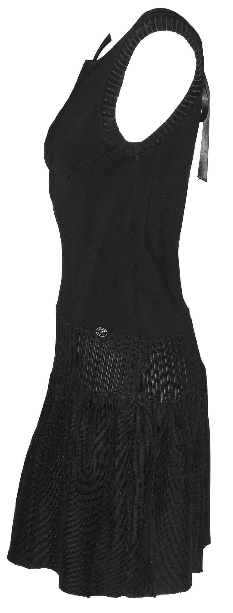 Chanel black sleeveless dress includes a V peek a boo back that is tied with a black satin bow.  This dress is ribbed at the front V neck and the slight drop sleeves.  With a drop waist to the hips this dress is gathered with mini ribbed pleats then