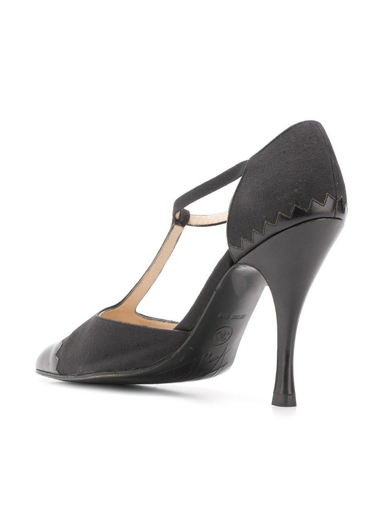 Crafted from a combination of black calf leather and canvas, these vintage pumps by Chanel are for the fashion forward, featuring a 10cm stiletto heel and branded insole, a pointed toe with a T-strap accentuating the front, and an ankle strap