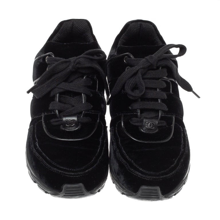 The time to feel trendy is now as Chanel brings you these superhit sneakers in black. They are crafted from velvet with leather trims, detailed with lace-ups and signature CC logo on the vamps, and set on highly comfortable rubber soles. You are