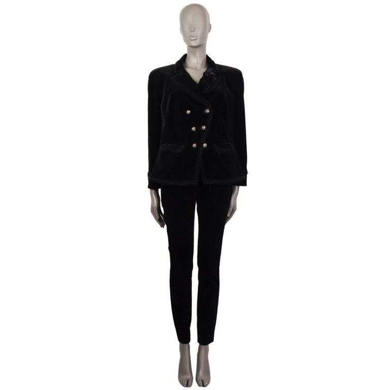 CHanel double-breasted velvet blazer in black ctoon (99%) and elastane (1%). With peak collar, short.fringe trims, two flap pockets on the front, and diagonal front seam, Closes with embellished CC buttons in antique gold, black and white metal and