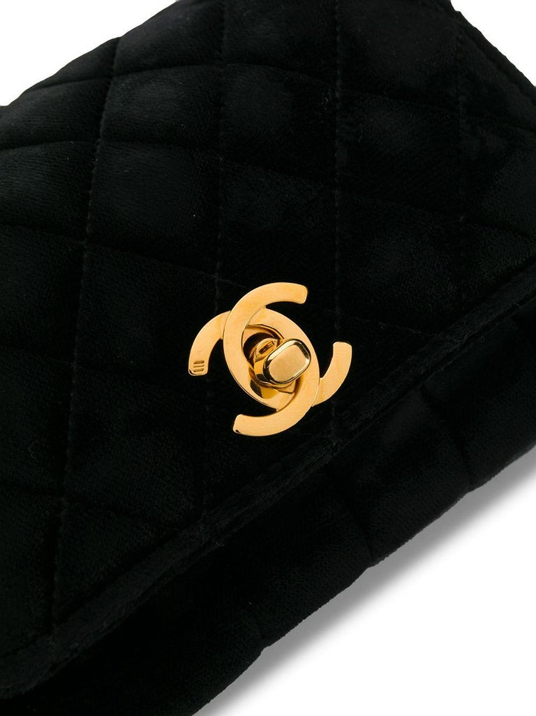 Crafted in France from luxurious black velvet, this pre-loved, mini shoulder bag by Chanel features a diamond quilted finish, a practical fold-over front flap and the iconic interlocking CC Mademoiselle twist-lock stitched decoratively onto the