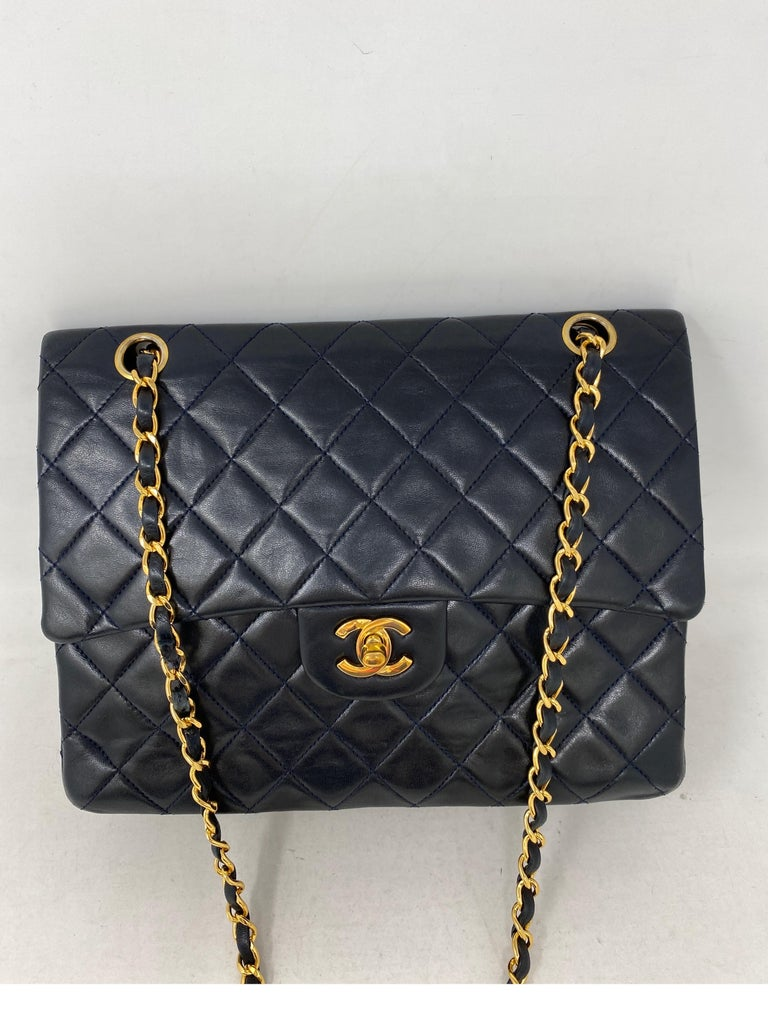 Chanel Black Vintage Double Flap Bag. Larger size. Gold hardware. 24 kt gold plating on hardware and chain strap. Excellent condition for a vinatge bag. Lambskin leather. Interior clean. Guaranteed authentic.