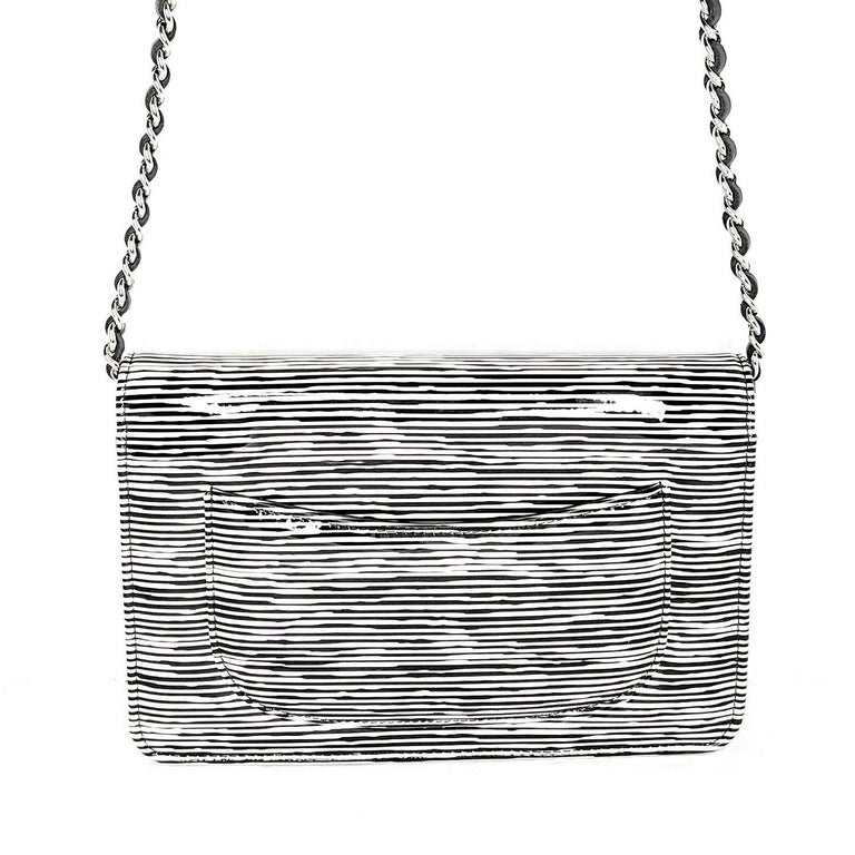 From the Resort 2014 Collection; Chanel Wallet on Chain Striped Patent, crafted from black and white striped printed patent Calfskin leather, features woven-in leather chain strap, interlocking CC logo on its flap, and silver-tone hardware. Its