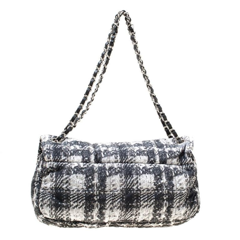 Chanel's Flap bags are the most iconic handbags. The black and white Soft Shell flap bag is crafted from nylon and features a tweed print all over it. It flaunts a vertical quilted pattern on the exterior and has a double chain and leather woven