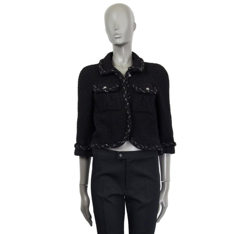 Chanel cropped tweed open jacket with braided chain trim in black wool (100%). Has one top button and raglan shoulders. Lined in black silk with antique silver-tone metal chain detail on the bottom. Has been worn and is in excellent condition.   Tag