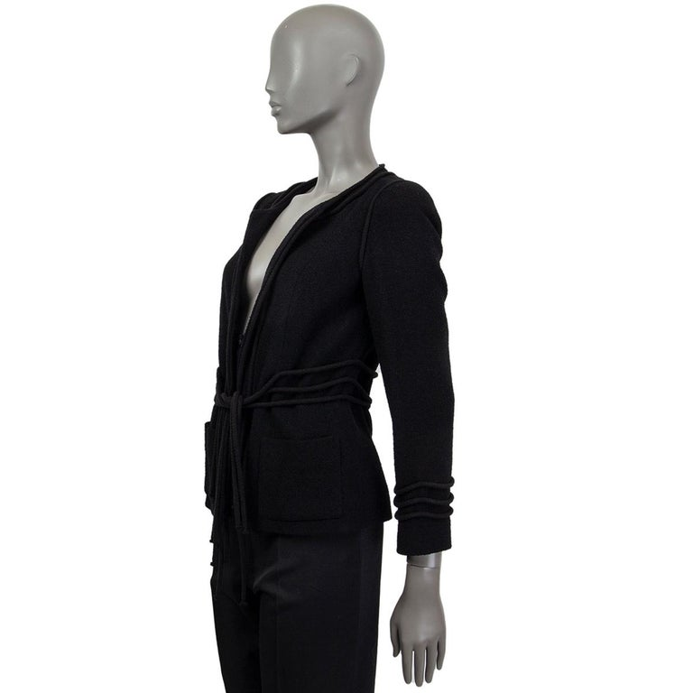 Chanel collarless tweed jacket in black wool (85%) and nylon (15%) featuring three cords around the waist and around the cuffs. Closes with three Camelia -Buttons in the middle and two patch pockets at front. Lined in black silk (100%). Has been