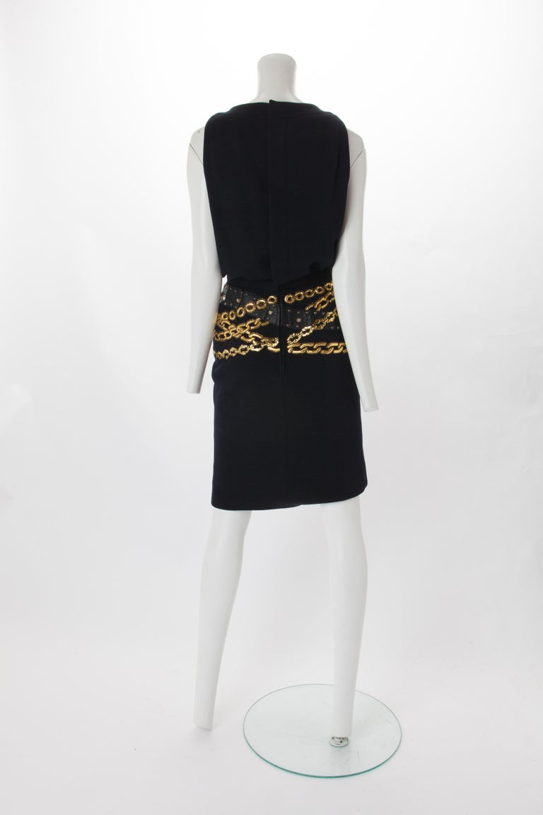 Chanel Black Wool Dress with Gold Chain Trompe L'oeil, 1985. Crew neck wool dress with buttons down the center of the bodice and two buttoned pockets at bust. Features waist band with black leather and gold chain detail wrapping around the hip.