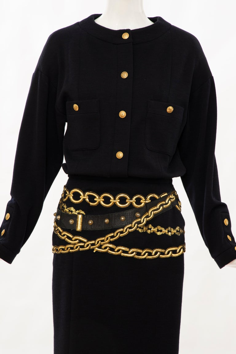 Chanel Boutique, Circa: 1990's black wool dress with long sleeves, interlocking CC button accents and dual patch pockets at front, gold metallic trompe l'oeil chain belts at waist, concealed buttons and zip closure at back and fully lined in black