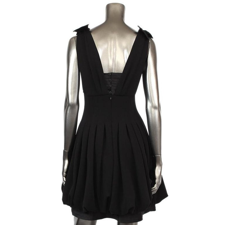 Chanel sleeveless knee-length cocktail dress in back wool (100%) with top and bottom part in black silk (100%). Opens with four rhinestone buttons and a hidden zipper on the back. Lined in silk. Has been worn and is in excellent condition.  Tag Size