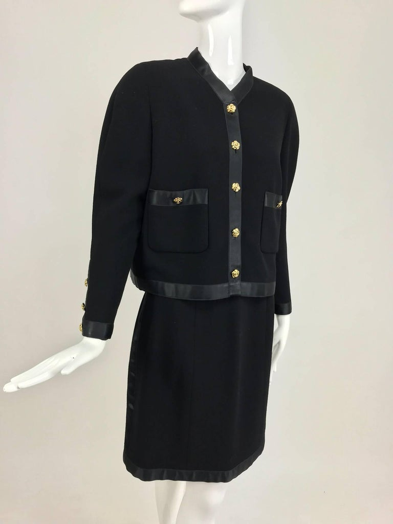 Chanel black flat weave wool with satin trim skirt suit from the 1990s...Cropped boxy jacket with jewel neckline, logo buttons at front and cuffs...The jacket is trimmed in wide black satin giving it a tuxedo style...The skirt has a satin waist