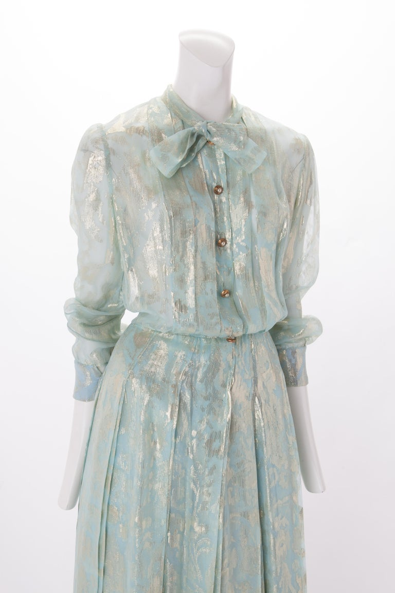 Chanel Blue and Gold Silk Lamé Dress with Self-Tie at Neck, c.1980s. Sheer full-length pale blue and gold silk lame dress with pleated plackets at center front of bodice. Features gold buttons with pearl center down front, mandarin collar with