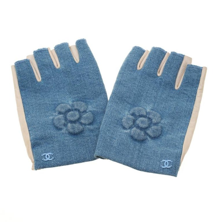 Complete your chic ladylike looks with these utterly feminine and elegant gloves from the house of Chanel. They are rendered in a fingerless silhouette with denim and leather. These gloves are embossed with the signature Camellia flower and carry