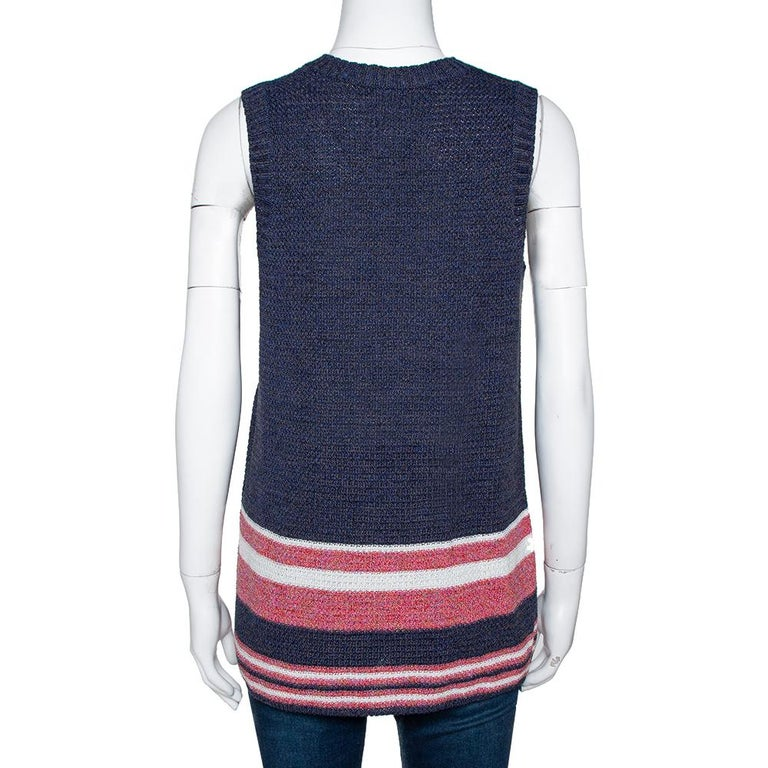 Casual and exuding elegance, this sleeveless top hails from the iconic house of Chanel. Crafted from a luxurious cotton-blend, it carries lovely shade of blue. The exterior has a striped detail near the hemline. It is styled with v-neckline, broad