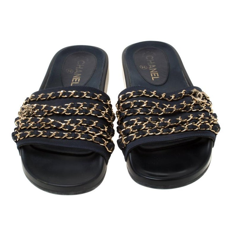 Stay comfortable throughout the day with minimal and effortless luxury in these Chanel Marine slides. Crafted in blue fabric front strap and a black rubber sole, these slides feature gold-tone chains woven with leather on the uppers.  Includes: The