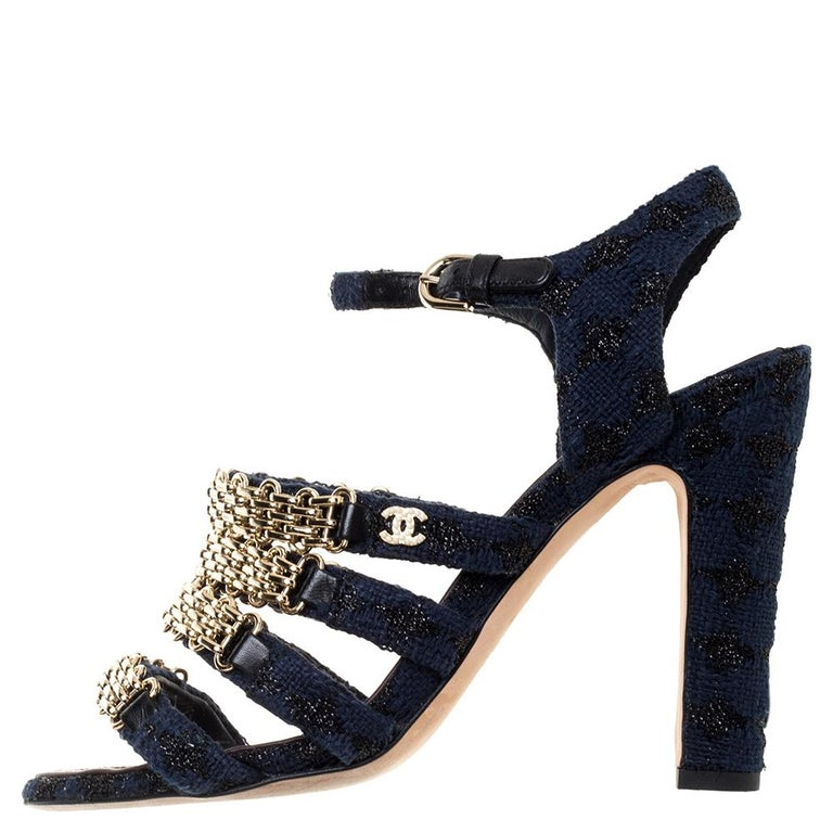 Flaunt this must-have Chanel creation as you step out in style. This classic fabric pair features chain detailing on the front straps with 11 cm heels and a buckle ankle strap closure. These striking blue-hued sandals are further detailed with a CC