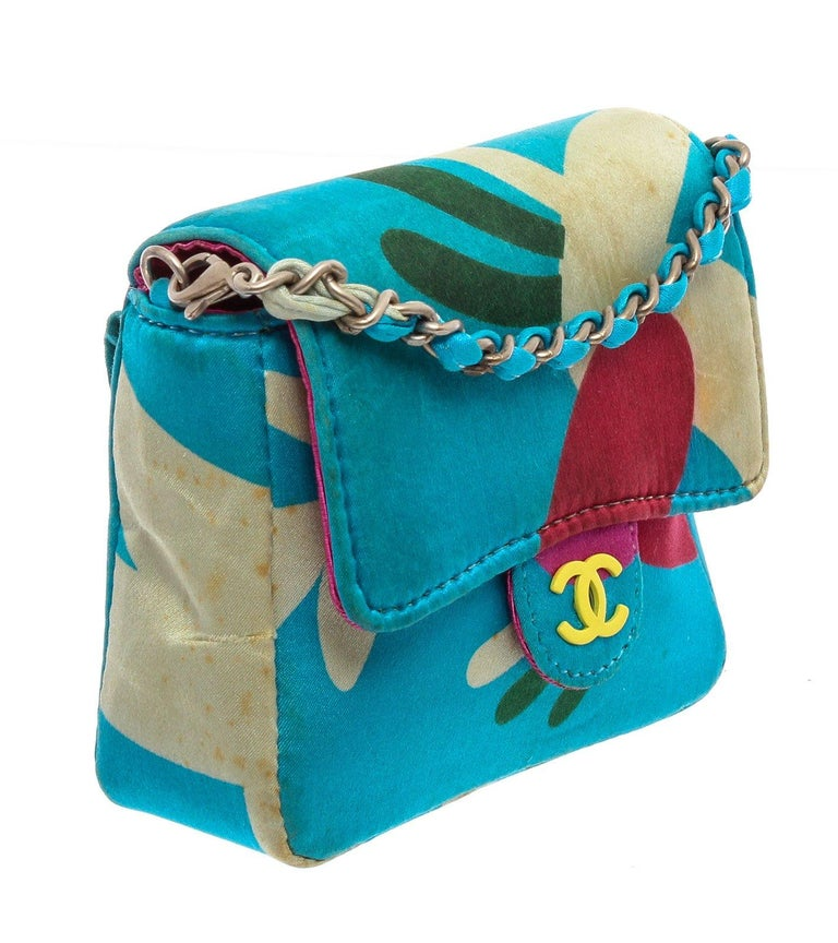 Chanel Blue Multicolor Satin Mini Messenger Pouch features a satin multicolor print with a skinny belt loop on the back and has a detachable chain strap that can be worn over your shoulder. Please note: Some staining throughout, please see