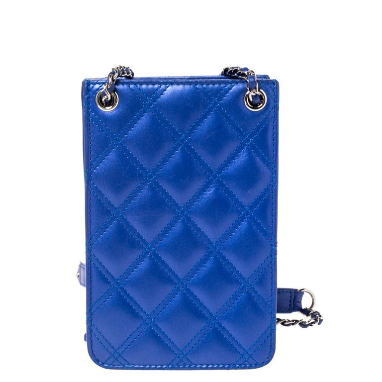 This phone holder crossbody bag is a true Chanel piece brimming with elegance. The blue quilted leather gives it a glistening appeal. It features an embroidered CC logo on the front and an interwoven chain-link strap with leather shoulder rest.