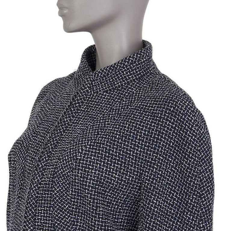 Chanel 3/4-sleeve tweed blaze in black, blue, and white wool (50%), polyester (20%), cotton (12%), and nylon (8%). With mandarin collar, slightly puffed shoulders, two pockets on the lower front, and signature chain around the inside of the hemline.