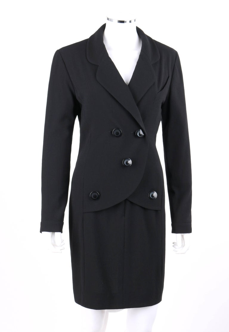 Chanel Boutique c.1980's black wool crepe double breasted one piece dress suit. Designed by Karl Lagerfeld. One piece mock blazer and pencil skirt dress suit. Rounded notched lapel collar. Long sleeves with single button closure at cuff. Five front