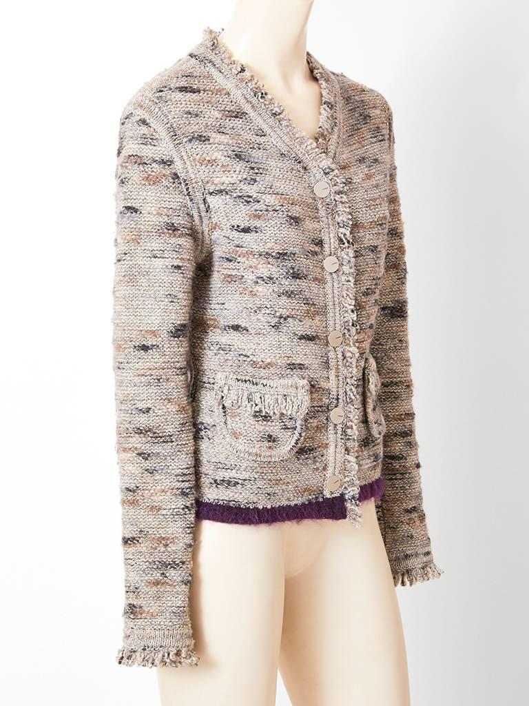 Chanel boutique, wool knit, tweed jacket/ cardigan having a v neckline, front button closure, curved patch pockets and a knit fringe decorating the neckline, cuffs, center front and pockets.