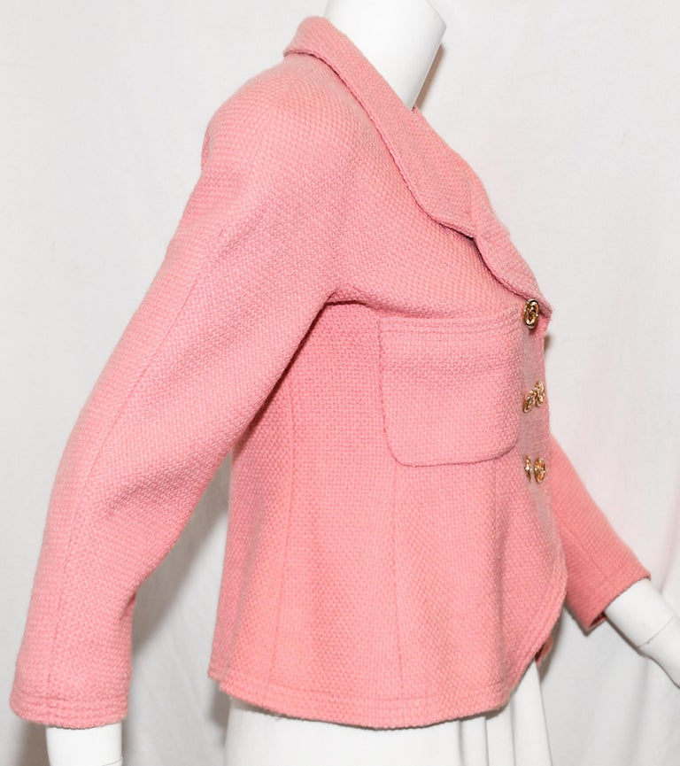 Chanel Boutique double breasted cropped jacket contains 6 gold tone CC buttons, for closure. Jacket includes 2 patch pockets at chest.  This garment is lined in pink CC logo silk.  It contains rounded notch collar.  This jacket is in excellent