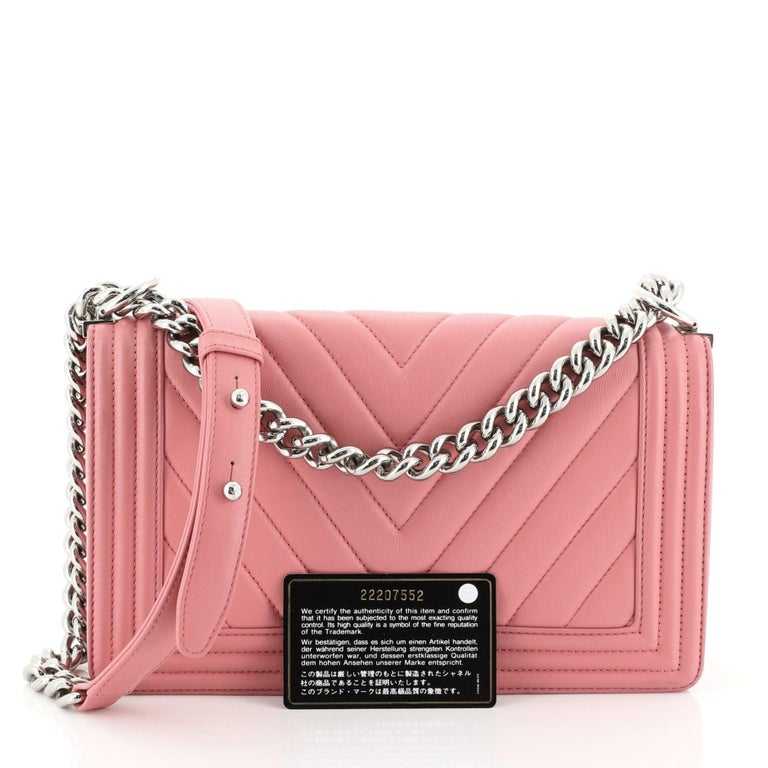 This Chanel Boy Flap Bag Chevron Calfskin Old Medium, crafted from pink chevron calfskin leather, features long chain strap with leather shoulder pad and silver-tone hardware. Its CC push-lock closure opens to a gray fabric interior with slip