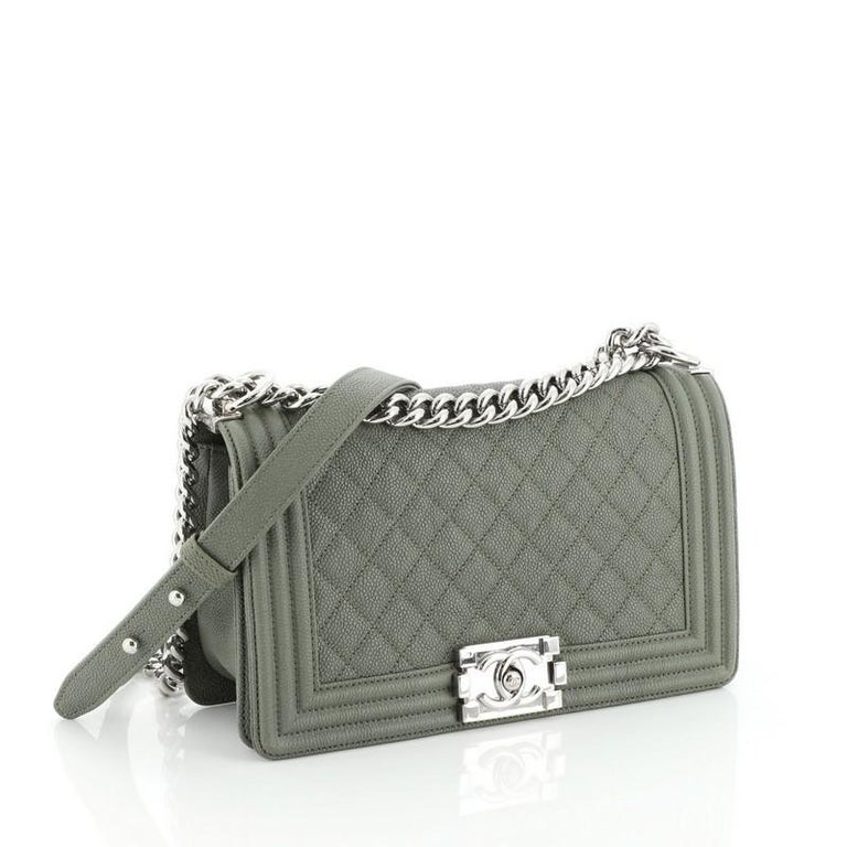This Chanel Boy Flap Bag Quilted Caviar Old Medium, crafted from green quilted caviar leather, features chain link strap with leather shoulder pad and silver-tone hardware. Its CC boy logo push-lock closure opens to a green fabric interior with slip