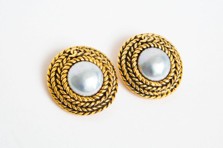 These large and 80's Chanel braided gilt metal and center baroque gray faux pearl have the small iconic CC's on the top that are interwoven. They are button clip on earrings and marked. They are 1.5
