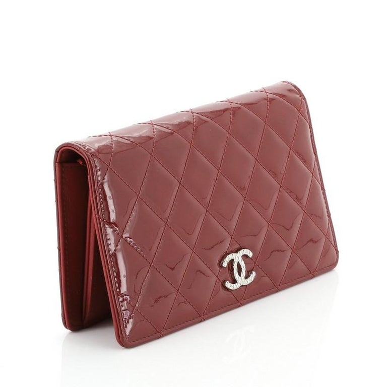 This Chanel Brilliant L-Yen Wallet Quilted Patent, crafted from red quilted patent leather, features textured CC logo and silver-tone hardware. Its opens to a red leather interior with multiple card slots and slip pockets. Hologram sticker reads: