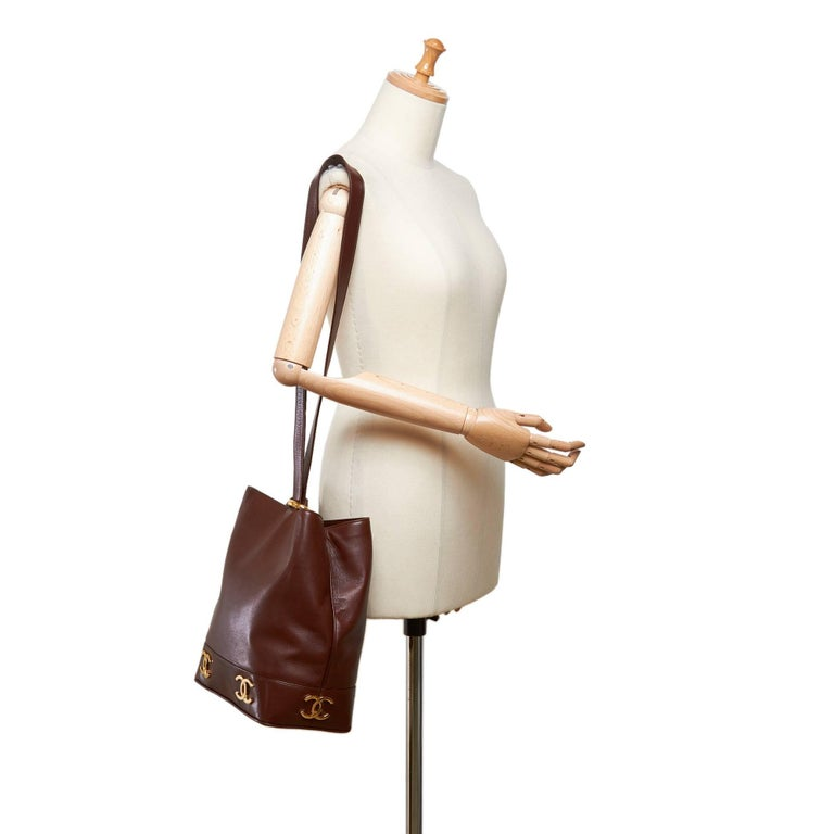 """- Vintage 90s Chanel brown leather bucket bag.   - Featuring single strap with a gold-toned """"eyelet"""" hardware fastening.  - Gold-toned """"CC"""" hardware on the bottom.   - Interior pocket zip closure.   - Size 28cm x 25cm x 14cm.   - Code: 298765.   -"""