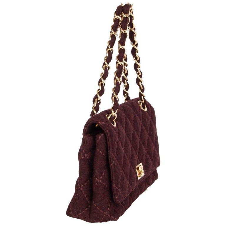 Chanel Vinatge shoulder bag in raisin wool jersey featuring light gold-tone chain strap and CC turn-lock. Lined in burgundy calfskin with on ezipper pocket against the back and one open pocket against the front. Slip pocket on the back side. Has