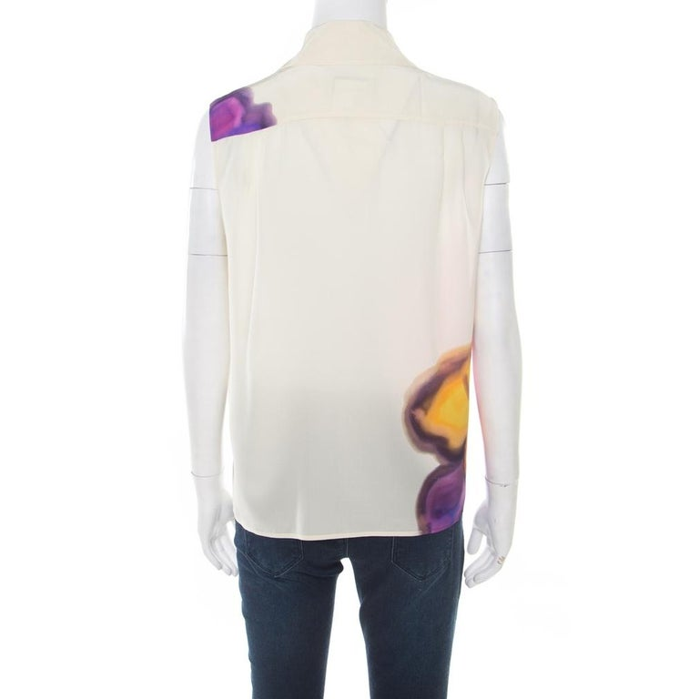 This lovely blouse from Chanel deserves a special place in your wardrobe! The sleeveless butter cream blouse is made of 100% silk and features a beautiful floral watercolour print on it. It flaunts sharp collars and front button fastenings. Pair it