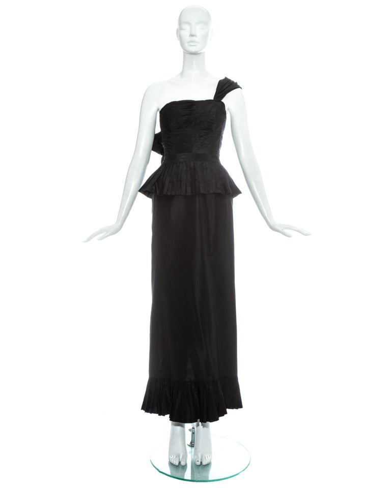 Chanel by Karl Lagerfeld; black silk taffeta evening dress. Bustier with horizontal pleats, internal boing, box pleated peplum and draped shoulder strap with decorative bow fastening. Maxi skirt with box pleated trim, back vent with decorative bow